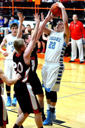 St. Elmo/Brownstown's Jacob Behrends takes a jumper over a pair of Beecher City defenders during the fifth-place game of the NTC tournament.