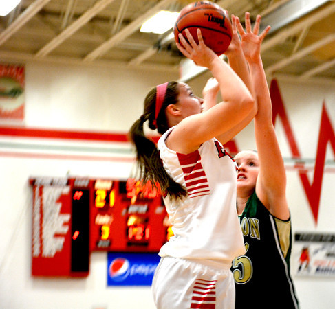 Effingham's Lauren Stephenson puts a shot up and above the defense of Mattoon's Kaitlyn Bath in the post.