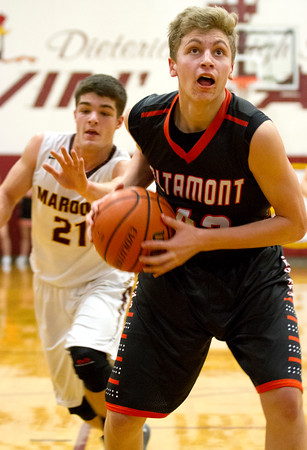Altamont's Sam Childerson eyes an open basket down low while Dieterich's Trenton Poe tries to close the gap.