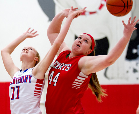 Effingham's Shelby Myers goes for a rebound over St. Anthony's Abbie Schmidt.