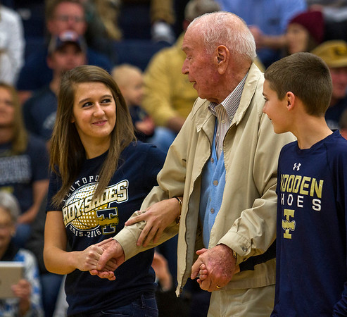 """Girls' basketball player Raegan Drees, left, and Kayden Althoff, right, escort 1944 Teutopolis alum Bill Dasenbrock to center court Friday, Jan. 6 during the """"Tradition Meets Today"""" ceremony, which sought to familiarize today's generation of basketball players to the long-time culture and success of Wooden Shoe basketball by introducing them to former players."""