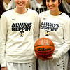 Teutopolis seniors Jamie Sandschafer and Shelby Thompson pose with the game ball from Teutopolis' 1,000th win as a program over Trenton Wesclin during a pregame ceremony, among a sea of former players and coaches.