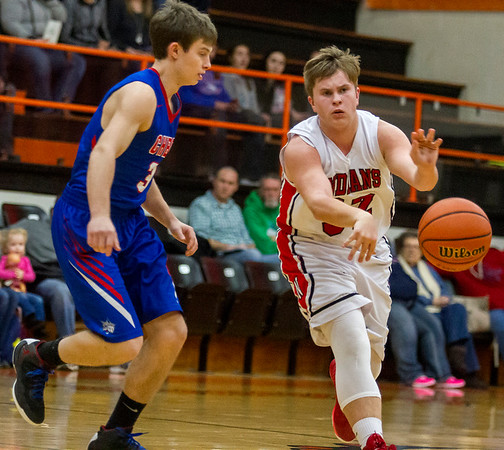 Neoga's Evan Fritcher makes a bounce pass while being guarded by Cowden-Herrick/Beecher City's Cody Grove at the National Trail Conference Tournament in Altamont.