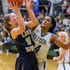 Mattoon's Sierra Thompson defends against Teutopolis' Sadie Bueker. Thompson recorded a double-double in the Green Wave's 66-58 win.