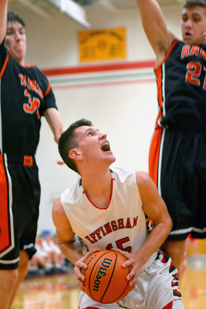 Effingham's Landon Wolfe looks to shoot between two Mt. Vernon defenders in the post during the Flaming Hearts' win.