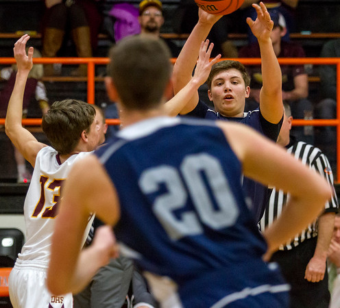 South Central's Trent Geiler passes it to teammate Trevor Markley (20) while being guarded by Dieterich's Bryce McClain.