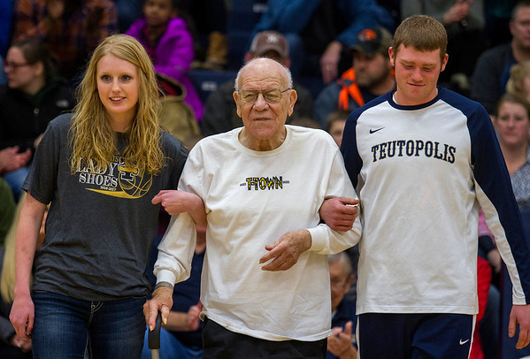 Jim Esker, center, a 1947 Teutopolis alum, is escorted out onto the high school basketball court Friday, Jan. 6 by his great-niece, senior girls' basketball player Jamie Sandschafer, left, and senior boys' basketball forward Blake Mette, right. Esker was one of nine players from the '40s honored during the Tradition Meets Today event.