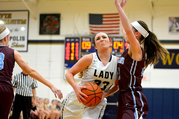 Teutopolis' Shelby Thompson cuts through a pair of St. Joseph-Ogden defenders at Teutopolis High School.