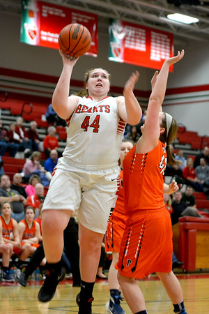 Effingham's Shelby Myers posts up Pana's Grace Sims and scores at the Effingham Round Robin Tournament. The Lady Hearts beat Pana and won the tournament.