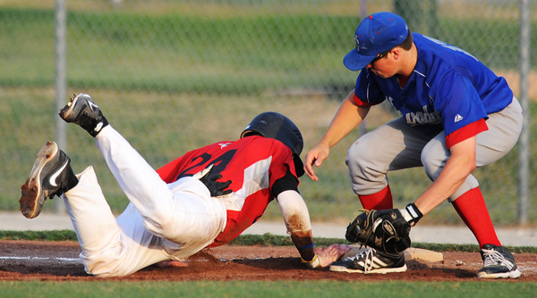 Globe/T. Rob Brown<br /> Joplin Outlaws runner Max Ayoub safely slides back to first against a Nevada Griffons (17) pickoff attempt Tuesday evening, June 25, 2013, at Joe Becker Stadium.