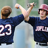 Globe/T. Rob Brown<br /> Joplin American Legion's Rex Whisner (left) and Nate Brummer share congratulations after they scored back-to-back runs against Carl Junction Tuesday evening, May 28, 2013, at Carl Junction High School's field.
