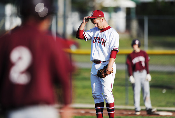 Globe/T. Rob Brown<br /> Joplin High School pitcher Adam St. Peter pauses for a moment while flanked by Rolla runners during Wednesday evening's game, April 24, 2013, at Joe Becker Stadium in Joplin.