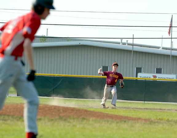 Dieterich Post 628 shortstop Paul Thoele throws out a runner in the foreground against Effingham Post 120.