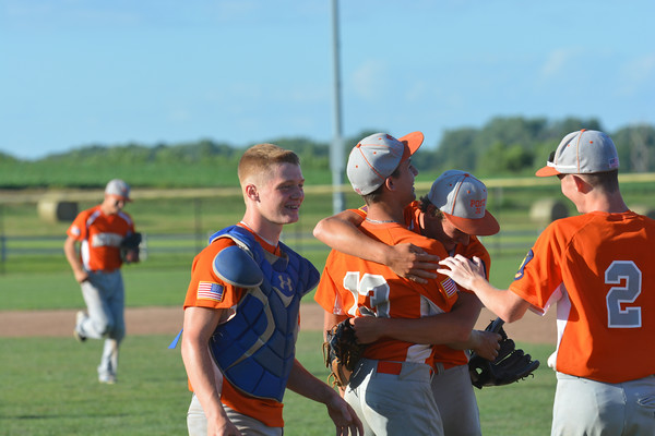 Newton Post 20 pitcher Tim Weber (center right) hugs third baseman Luke Geier (13) while catcher Mitch Bierman (left) approaches Mike Carr (2) moments after Newton downed Highland Post 439. Geier converted the final out of a 10-7 win.