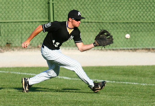7-9-14<br /> American Legion baseball<br /> Logan Macaluso scoops up the ball in the outfield.<br /> Kelly Lafferty   Kokomo Tribune