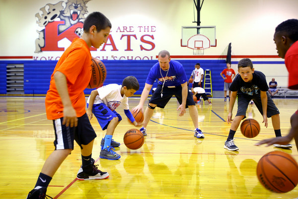 7-23-14 <br /> KHS boys basketball coach Matt Moore holding a basketball clinic for kids in grade 1-8. Cameryn Smith, Jon Callane, Hayden Smith and Jamari Patterson getting instruction from coach while doing a drill.<br /> Tim Bath | Kokomo Tribune