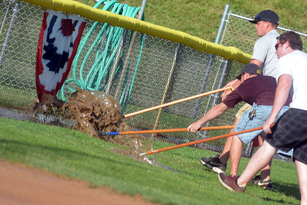 IHSA officials and workers attempt to clear off the field at East Peoria's Eastside Centre to resume the Class 1A championship game between Milledgeville and Cumberland. The game never resumed, as the field was deemed unplayable, and Cumberland lost 5-4 in five innings.