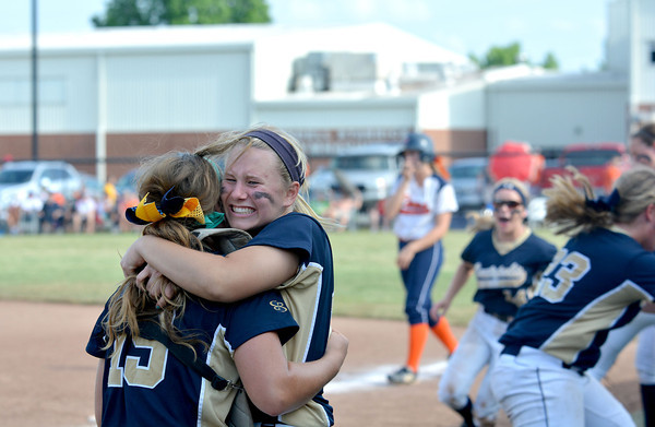 Teutopolis' Mackenzie Wermert hugs catcher Anni Borries (19, left) while other Lady Shoes react moments after the final out of their 2-1 Class 2A Johnston City Super-Sectional victory over Carterville.