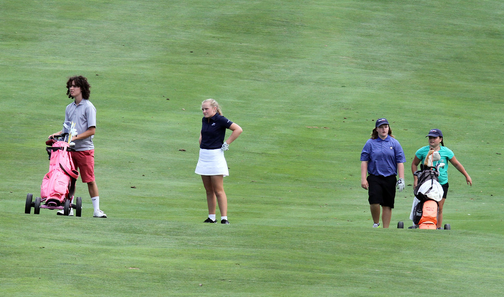 . Lowell Junior City Golf Tournament at Mount Pleasant. Morgan Smith, second from left, and Molly Smith, third from left, approach the 18th green with their caddies. (SUN/Julia Malakie)