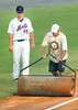 #45, Jon Leroux, of the K Mets watches as a member of the ground crew attempts to dry out the field and firm up the basepaths before game. Photo by Ned Jilton II