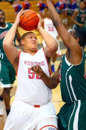 12-27-13   ---  Kokomo HS vs Lawrence North HS Boys Basketball. Brandon Wilson putting the ball up in the first quarter. Lawrence North's Terell Davis trying to block.<br /> <br />   KT photo | Tim Bath