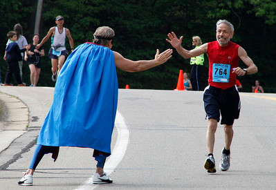 "A caped and masked ""superhero,"" Ken Dettloff, the YMCA fitness director, offers runner 764 a high-five on Bronson Blvd. near Maple Street, just beyond the halfway point during the Kalamazoo Marathon on May 6, 2012.  (Bradley S. Pines for John Lacko Photography) CONTACT: bspines@gmail.com"
