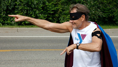 "A caped and masked ""superhero,"" Ken Dettloff, the YMCA fitness director, points to runners on Bronson Blvd. near Maple Street just beyond the halfway point during the Kalamazoo Marathon on May 6, 2012. (Bradley S. Pines for John Lacko Photography) CONTACT: bspines@gmail.com"