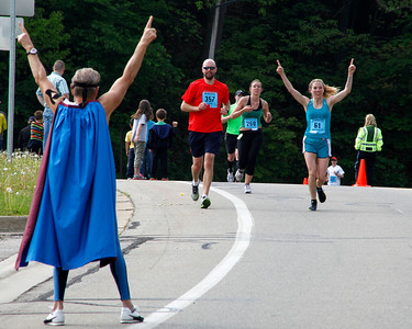 "Runner 61 responds to a caped and masked ""superhero,"" Ken Dettloff, the YMCA fitness director, on Bronson Blvd. near Maple Street, just beyond the halfway point during the Kalamazoo Marathon on May 6, 2012.  (Bradley S. Pines for John Lacko Photography) CONTACT: bspines@gmail.com"