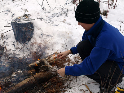 "Karen carefully warming up the ""Tim Curtis"" MRE.  Heated on edge of fire, ""Tim Curtis"" sandwich fortifies our resolve to clear more treefalls."