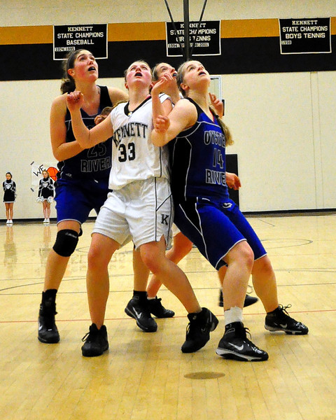 Moriah Heath (#33), of the Kennett Eagles, struggles for rebounding position with Oyster River defenders, during the February 25th game which the Eagles went on to defeat the visiting Bobcats 62-56.