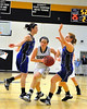 Co-captain Allie Wagner, of the Kennett High School Eagles, squeezes through Oyster River defenders, Izzy Gorham (L), and Bekah Schuman (R), during the February 25th game which the Eagles defeated the visiting Bobcats, 62-56.