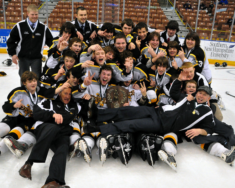 Players and coaches of the Kennett High School Eagles Hockey Team, from Conway, NH, celebrate with their championship plaque, after defeating the Bedford Bulldogs, 2-1, at the Verizon Wireless Arena, in Manchester, NH, to win the 2009-2010 NHIAA Division 3 Boys Ice Hockey Championship, on March 13th, 2010.