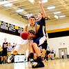 The Kennett Eagles senior co-captain, Brandon Frost, forces his way past a Merrimack Valley High School defender, during a January 13th game. The Eagles were defeated by the visiting Pride, 66-52.