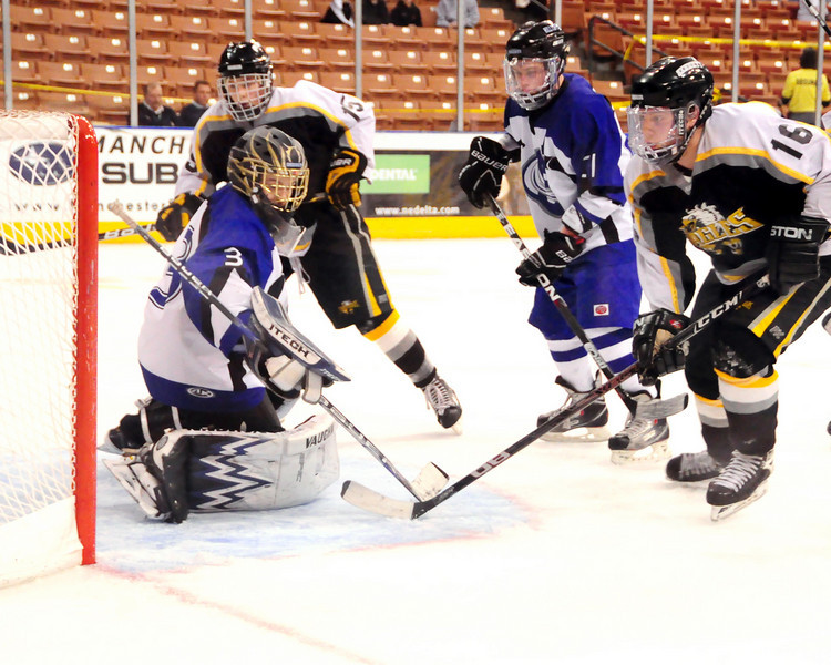 Kennett Eagles players, Cody Richard (#16 right), and Justin Munck (#15 left), try to get the puck past Somersworth goaltender, Peter Robertson, during the first period, of the NHIAA Division 3 Ice Hockey Championship Game, held at The Verizon Wireless Arena, in Manchester, NH, on March 13th, 2011. The Hilltoppers went on to score an 8-3, over the Eagles.