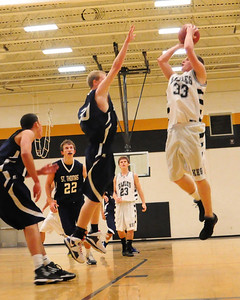 Kennett Eagles senior, Dustin Stewart, takes a jump shot over a St. Thomas Aquinas defender during the December 16th game held at Kennett High School, in Conway, NH. The visiting Saints went on to defeat the Eagles 65-43.