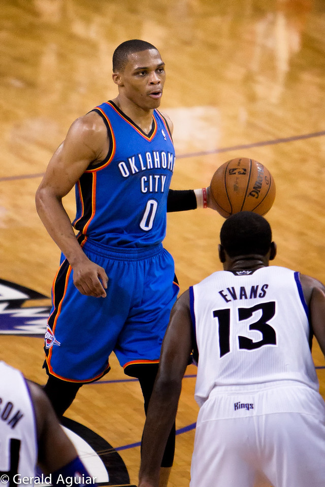 Westbrook getting ready to pass with his left hand to the right of Evans.