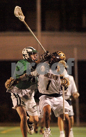 Baldwin #1 Dominique Alexander (1 goal) , Sophmore takes a check from Farmindale #4 James Hogan, Senior  in the final minutes of the 9-10 loss for Baldwin. Balwin vs Farmingdale, May 22, 2007. Photo by Kathy Leistner