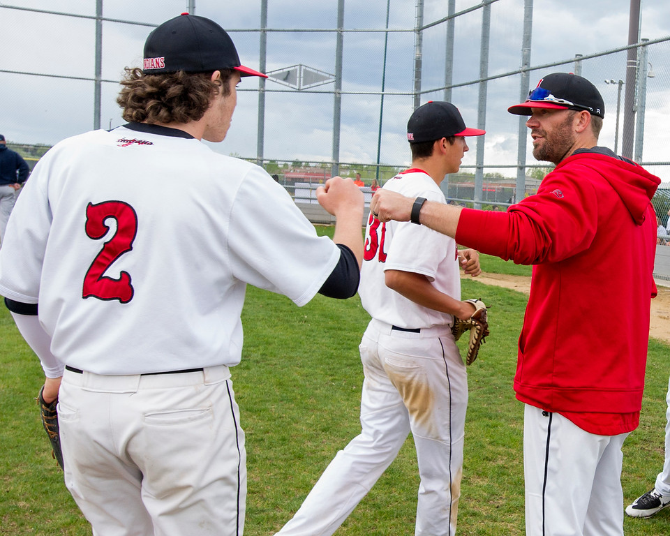 . Loveland head baseball coach Jerod Cronquist welcomes Kellen Bakovich (2) back to the dugout between innings Tuesday afternoon May 10, 2016, as Cronquist\'s team faced Ralston Valley at Centennial Park in Loveland. (Photo by Michael Brian/Loveland Reporter-Herald)