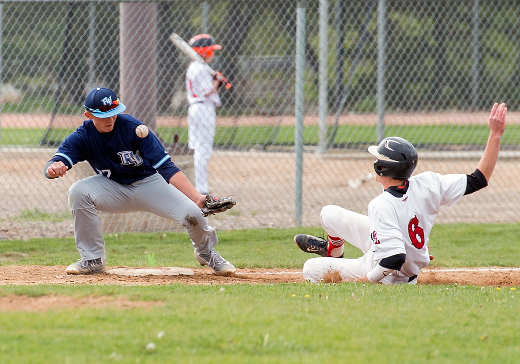 . Loveland\'s Ben Newton (6) safely slides into third base as Ralston Valley\'s Nick Levensteins (27) can\'t corral the throw Tuesday afternoon May 10, 2016, at Centennial Park in Loveland. (Photo by Michael Brian/Loveland Reporter-Herald)