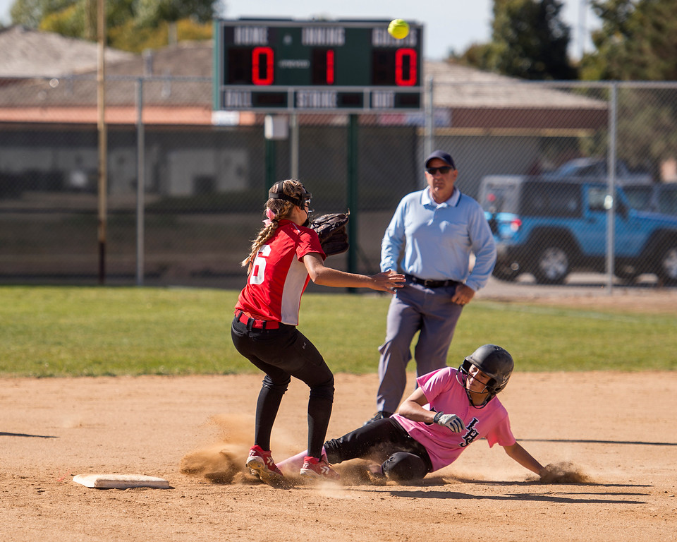 . Loveland\'s Tatum Rembao(5) slides safely into second base as the ball sails over the head of Fairview\'s Tea Valdez (6) Saturday morning Oct. 8, 2016 at Centennial Park in Loveland. The Indians won, 7-0. (Photo by Michael Brian/Loveland Reporter-Herald)