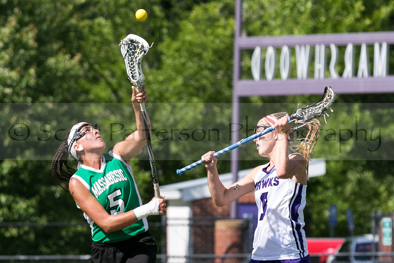 Marshwood's Reagan Nichols and Massabesic's  Maquila DiMastrantonio fight for control of the ball at the Class A South Lacrosse Final held at Marshwood High School Wednesday. Photo by Scott Patterson/Fosters.com