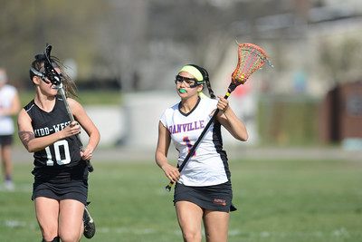 Danville's Avani Chopra runs up the field past Midd-West's Lyndsey Schenck during Monday's lacrosse match.