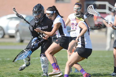 Midd-West goalie Kierstin Klingler tries to kick the ball away from Danville's Kara Bergerstock during Monday's lacrosse game in Danville.