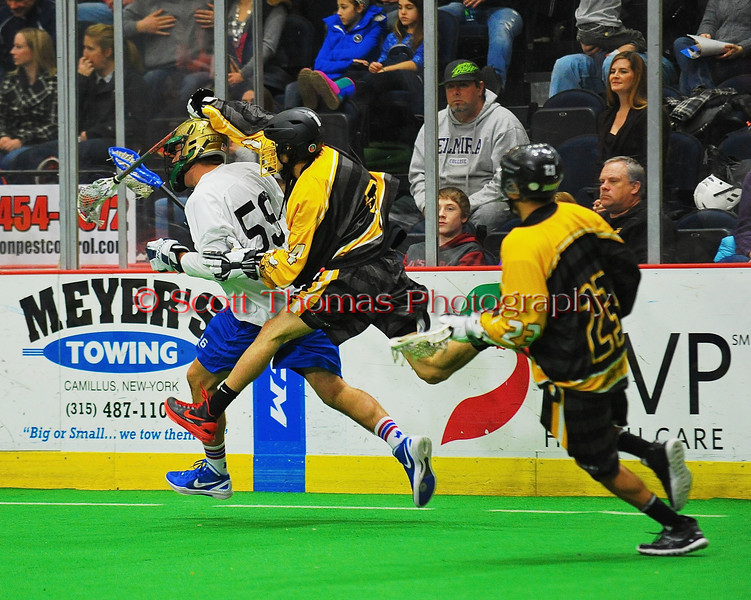 Syracuse Stingers Tyler Hill (14) checks a NYC Lax All-Stars player at the Onondaga County War Memorial in Syracuse, New York on Thursday, February 21, 2013.