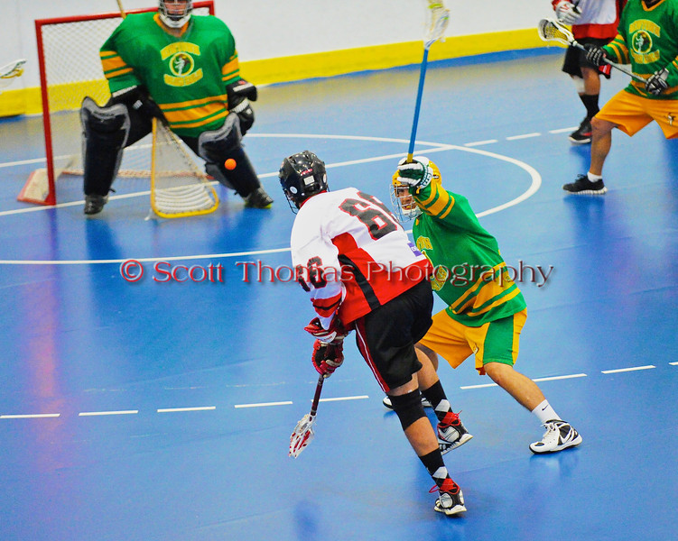 "Onondaga Redhawks Brett Bucktooth (66) shoots and scores against the Newtown Golden Eagles in the finals of the Can-Am Senior ""B"" Lacrosse league at the Onondaga Nation Arena near Nedrow, New York."