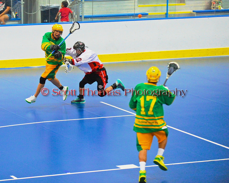 """Onondaga Redhawks Trevor Clark (2) checks a Newtown Golden Eagles player making a pass to teammate Kori Halftown (17) in the finals of the Can-Am Senior """"B"""" Lacrosse league at the Onondaga Nation Arena near Nedrow, New York."""