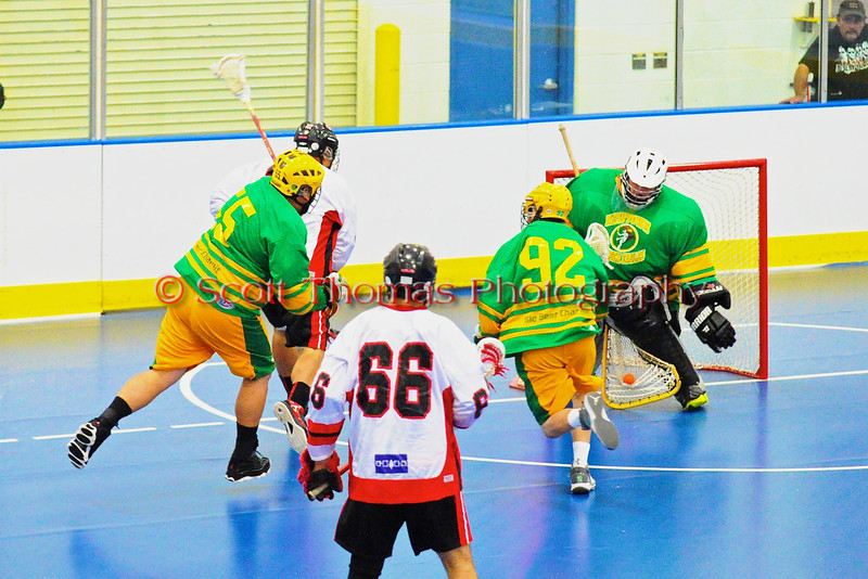 "Onondaga Redhawks player is stopped by Newtown Golden Eagles goalie Craig Seneca (30) in the finals of the Can-Am Senior ""B"" Lacrosse league at the Onondaga Nation Arena near Nedrow, New York."