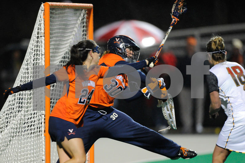 MAR 2, 2012 : Maryland Attacker Karri Ellen Johnson (18) scores a goal past Virginia Goalie Kim Kolarik (30) during action between the Virginia Cavaliers and the University of Maryland Womens Lacrosse match up at the Field Hockey and Lacrosse Complex at the University of Maryland in College Park, MD. The Terrapins defeated the Cavaliers 12-9.