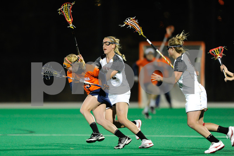MAR 2, 2012 : Virginia Attacker Josie Owen (3) battles Maryland's Beth Glaros (20) and Karri Ellen Johnson (18) during action between the Virginia Cavaliers and the University of Maryland Womens Lacrosse match up at the Field Hockey and Lacrosse Complex at the University of Maryland in College Park, MD. The Terrapins defeated the Cavaliers 12-9.