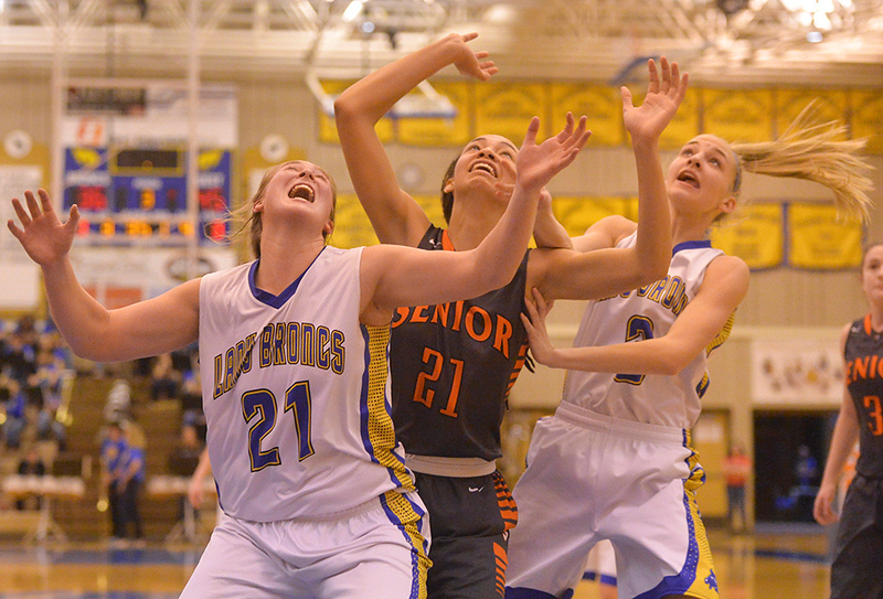 Justin Sheely | The Sheridan Press<br /> Sheridan's Jordan Christensen (21) and Katie Ligocki (3) try to rebound against Senior High School's Bailey Eleazer during the Lady Broncs' home opener at Sheridan High School Friday, Dec. 15, 2017. The Lady Broncs lost to Billings Senior 64-59.